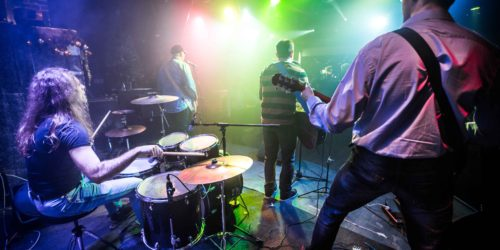 Band performs on stage, rock music concert in a nightclub
